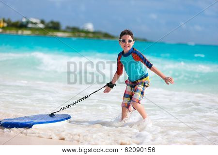 Little boy on vacation having fun surfing on boogie board