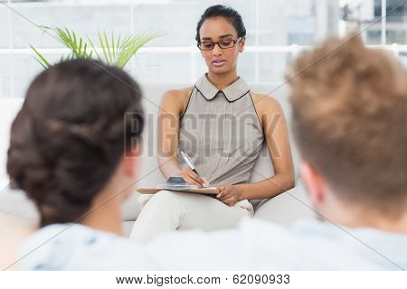 Therapist talking with couple on the couch in therapists office