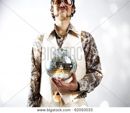 Instagram style portrait of a retro man in a 1970s leisure suit and sunglasses holding a disco ball - mirror ball