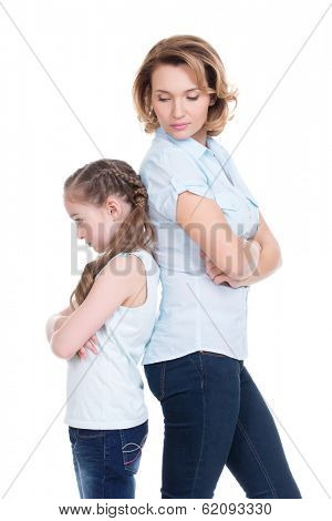 Sad mother and daughter having problem or quarrel standing back to back studio isolated on white