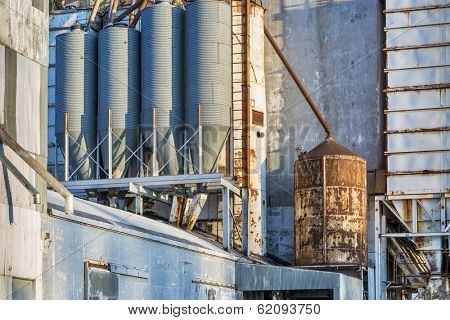 industrial background - exterior of old grain elevator with pipes, ducts, ladders and chutes