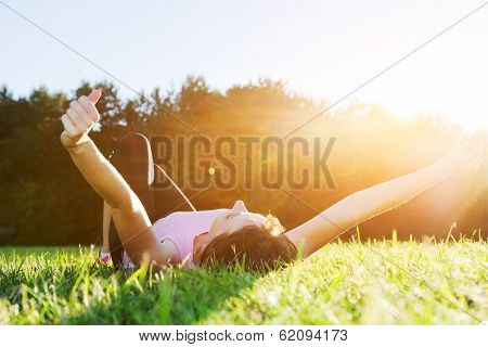 Young beautiful woman lying and stretching on the grass at spring summer sunset. Relaxation, balance and harmony.