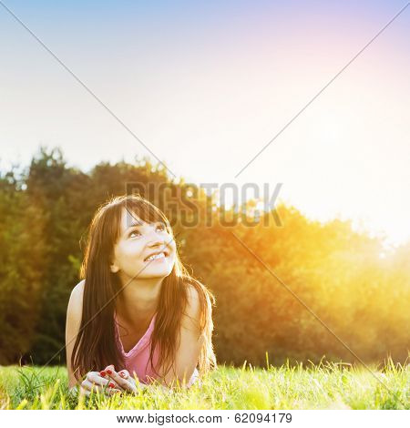 Young beautiful woman smiling and lying on the grass at summer sunset looking at the sky. Natural happiness, fun and harmony.