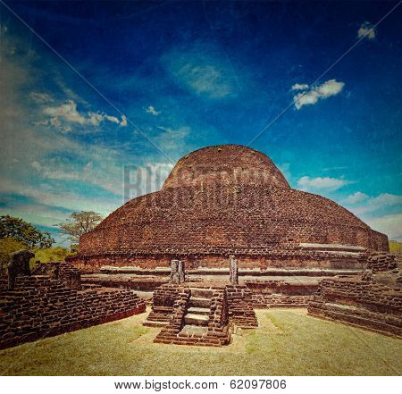 Vintage retro hipster style travel image of ancient Buddhist dagoba (stupe) Pabula Vihara with grunge texture overlaid. Ancient city of Pollonaruwa, Sri Lanka