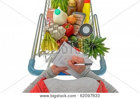 Overhead photo of a woman checking her shopping list with a trolley full of fresh food, isolated on a white background.