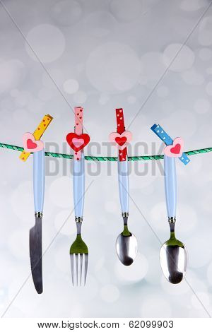 Cutlery dried on rope on bright background