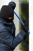 foto of sneaky  - A masked burglar trying to open the window with a plastic stick - JPG