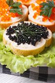 foto of butter-lettuce  - Sandwiches with red and black fish caviar on lettuce macro vertical - JPG