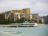 stock photo of waikiki  - Boat and canoe parked close to hotels of Waikiki Beach.