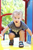 stock photo of playground  - Child toddler playing at an outdoor playground park in summer or spring