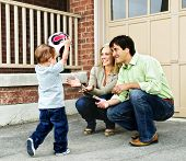 foto of bounce house  - Happy young family playing soccer with toddler on driveway - JPG
