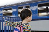 stock photo of passenger train  - Child waving to a passing or leaving train at train station - JPG