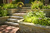 stock photo of planters  - Natural stone landscaping in home garden with stairs - JPG