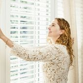 stock photo of curtain  - Happy woman looking out big bright window with curtains and blinds - JPG