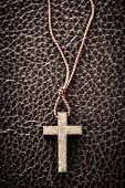 Closeup of simple wooden Christian cross necklace on leather bound holy Bible