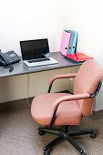 foto of spartan  - Workstation in office with swivel chair desk and laptop computer - JPG