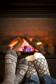 stock photo of cuddle  - Feet in wool socks warming by cozy fire - JPG
