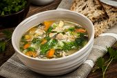 stock photo of vegetable soup  - Chicken rice soup with vegetables in bowl and bread on rustic table - JPG
