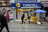 KADIKOY, TURKEY - SUNDAY, MARCH 9, 2014: Pedestrians walk past an Turkcell mobile telephone retail o