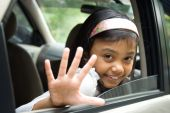 picture of say goodbye  - portrait of asian little girl waving hand from inside of a car saying goodbye as she is leaving for a vacation - JPG