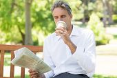 Businessman drinking coffee while reading newspaper in the park
