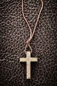 picture of leather-bound  - Closeup of simple wooden Christian cross necklace on leather bound holy Bible - JPG