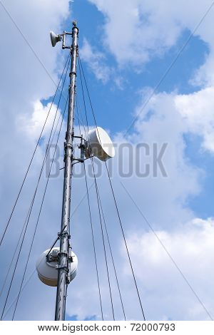 Communication Radio Tower With Devices Above Blue Sky Background