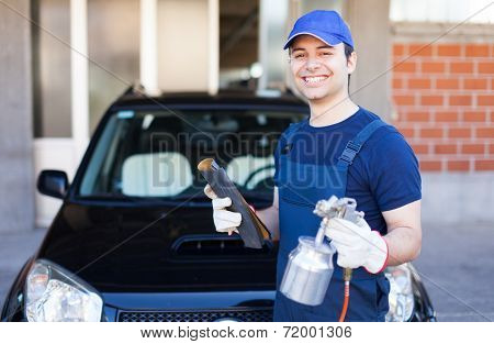 Car body repairer holding a spray gun and a sheet of sandpaper
