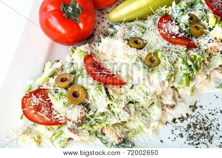 A Small Caesar Salad With Shredded Parmesan Cheese, Croutons And Tomatos