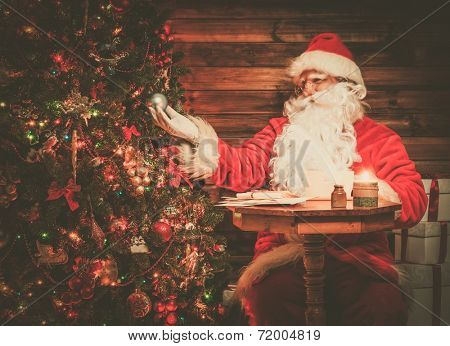 Santa Claus in wooden home interior looking at decorated Christmas tree