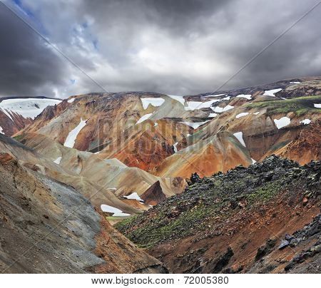July in Iceland. The famous Valley Landmannalaugar. Multicolored rhyolite mountains with the remnants of last year's snow