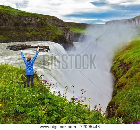 Powerful Gullfoss in Iceland. On the hillside woman thrilled looking at the boiling abyss