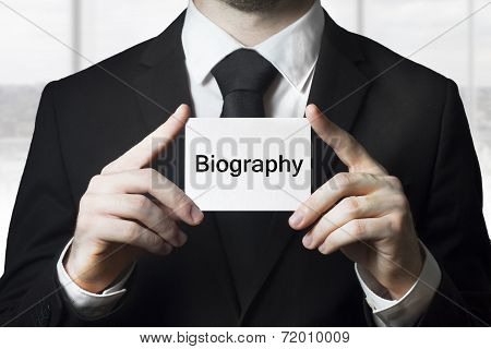 Businessman Holding Sign Biography