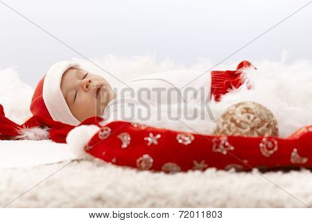 Newborn baby sleeping in santa hat, christmas decoration around.