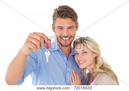 Portrait of happy attractive young couple holding new house key over white background