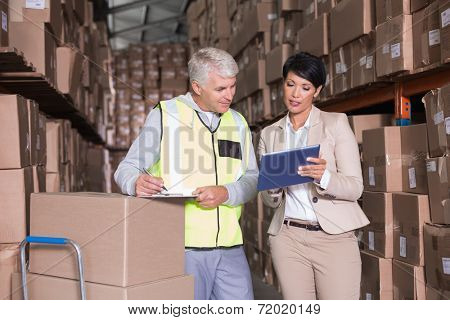 Pretty warehouse manager talking to foreman in a large warehouse