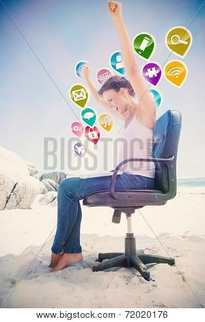 Cheering brunette using laptop on the beach sitting on swivel chair with colourful computer applications