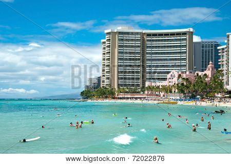 Tourist Sunbathing And Surfing On Waikiki Beach On Hawaii Oahu