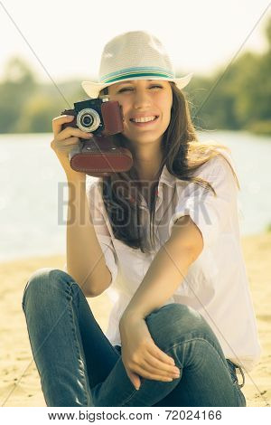 Young Woman Posing With Old Film Camera. Caucasian Hipster Girl In Hat