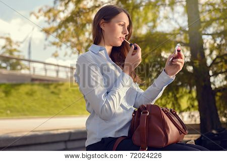 Attractive Young Woman Refreshing Her Makeup