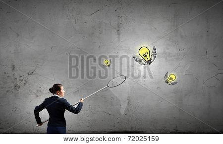 Young businesswoman catching light bulb with hoop