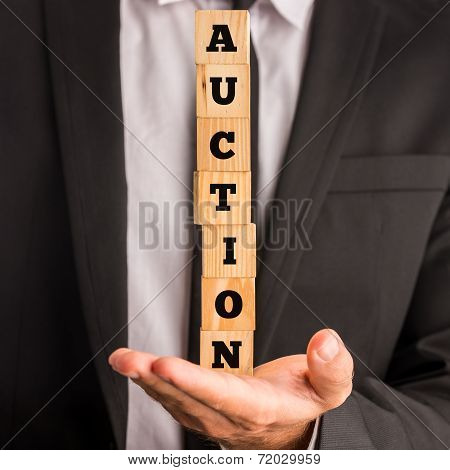 Businessman Holding Stacked Blocks Reading Auction