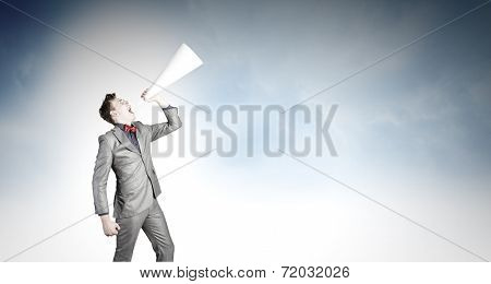 Young businessman screaming emotionally in paper trumpet