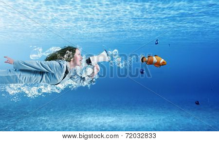 Young businesswoman in suit swimming in crystal blue water