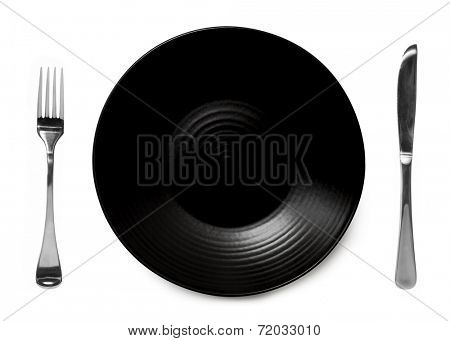 Black plate isolated on white with knife and fork.