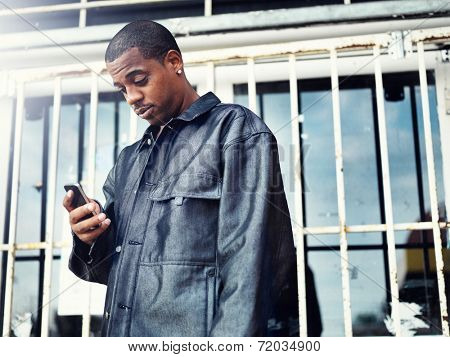 african american man with smartphone in front of abandoned store