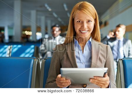 Smiling young woman with touchpad sitting in airport with two colleagues on background
