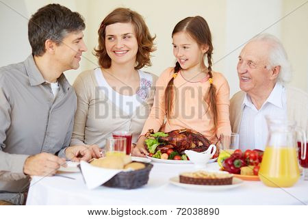 Big family looking at young man during traditional Thanksgiving dinner
