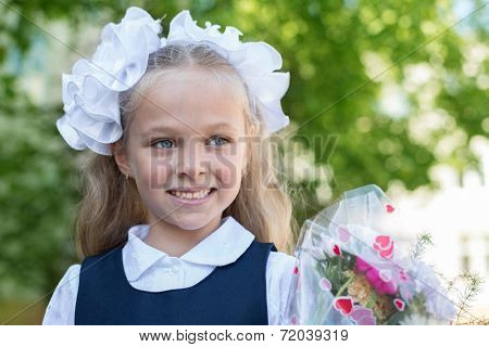 First grader girl with bows in the first day of school.