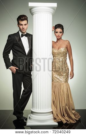 luxury couple posing in studio near column, ceremony concept
